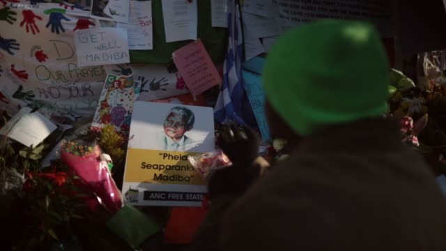 close up pull focus shot, a man prays at the tribute wall to nelson mandela outside the mediclinic heart hospital where he is being treated for a... - ハウテング州点の映像素材/bロール