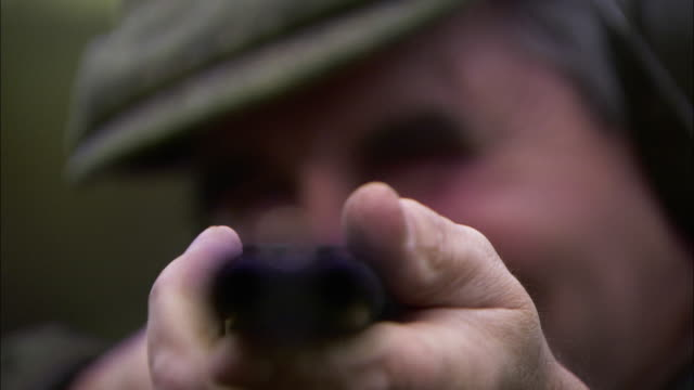 Close Up push-in - A marksman aims a double barrel shotgun. / London, England