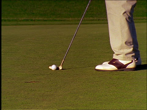 vídeos y material grabado en eventos de stock de close up putter hits golf ball into hole / man's feet visible - zapato de golf