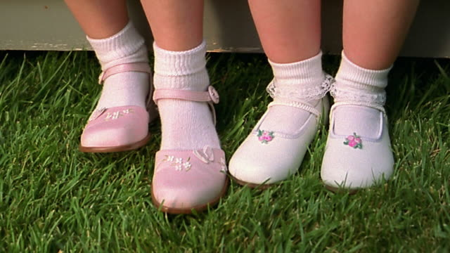 close up rack focus 2 small girls' feet in white dress shoes and socks on grass - shoes stock videos and b-roll footage
