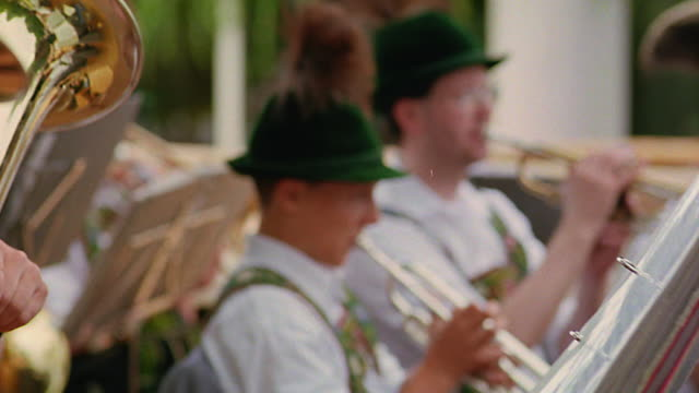 close up pan rack focus from man in german costume playing instrument to other musicians / bad kohlgrub, bavaria - traditionelle kleidung stock-videos und b-roll-filmmaterial