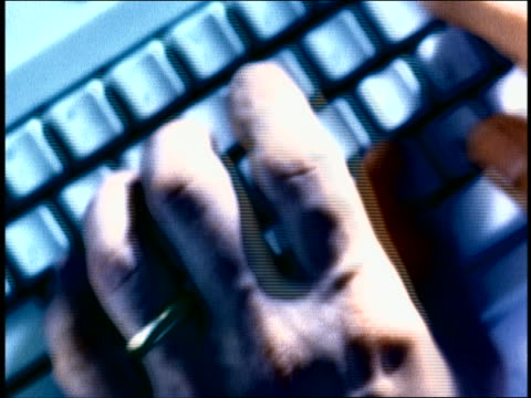 blue overexposed close up pan rack focus hands of man typing on computer keyboard - overexposed stock videos & royalty-free footage