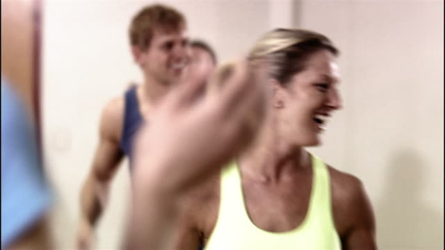 Close up rack focus instructor conducting step aerobics class / pan to student in class smiling and clapping