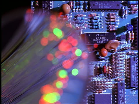 close up rack focus magnifying glass point of view bunch of fiber optics with pulsing lights / circuit board in background - fibra ottica video stock e b–roll