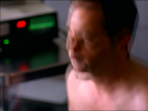 close up rack focus man with electrodes walking on treadmill in stress lab + heart monitor in background - 電極点の映像素材/bロール