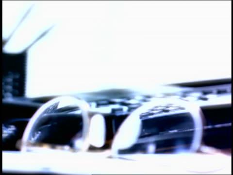 vídeos de stock, filmes e b-roll de overexposed close up rack focus man's hand picking up telephone + slamming it down / eyeglasses in foreground - superexposto