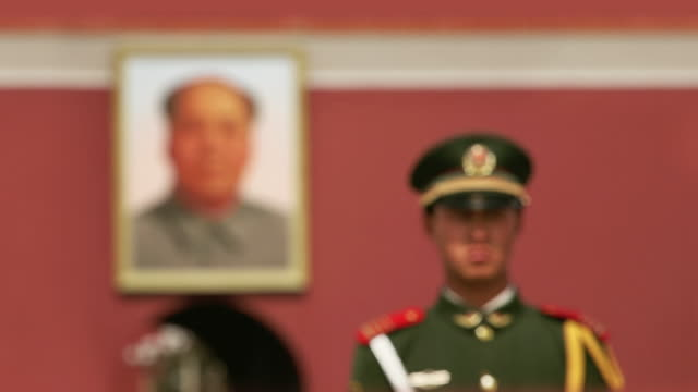 Close up rack focus military guard standing next to portrait of Chairmain Mao in Tiananmen Square/ Beijing, China