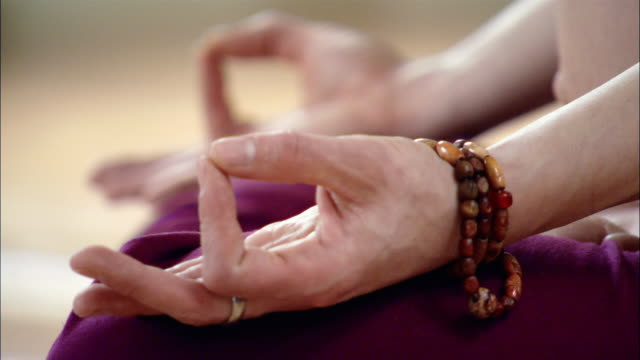 Close up rack focus on hands in guyan mudra