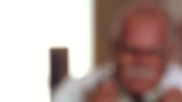 close up rack focus portrait senior hispanic male doctor in office - 年配の男性一人点の映像素材/bロール