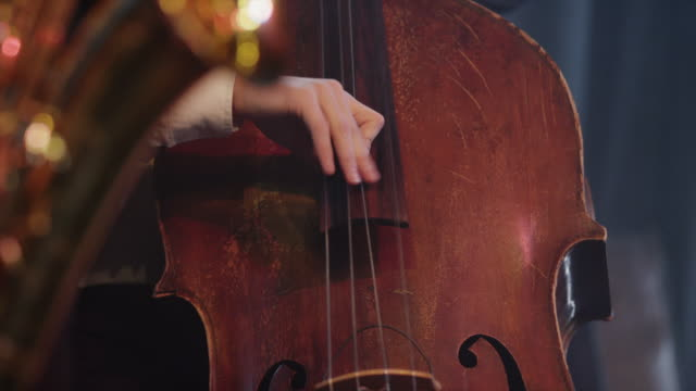 close up rack focus shot of man playing cello on stage / provo, utah, united states,  - provo stock videos & royalty-free footage