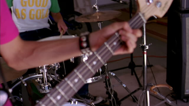 close up rack focus teenage boy playing bass guitar / pan teenage boy playing drums - 16歳から17歳点の映像素材/bロール