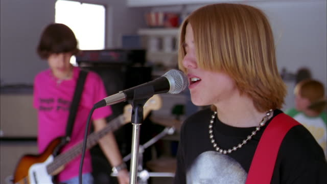 close up rack focus teenage boy singing into microphone / teenage boy playing bass guitar in background - rock and roll video stock e b–roll