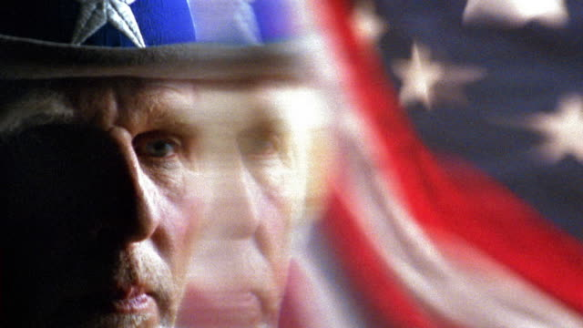 close up rack focus uncle sam in front of american flag - uncle sam stock videos & royalty-free footage