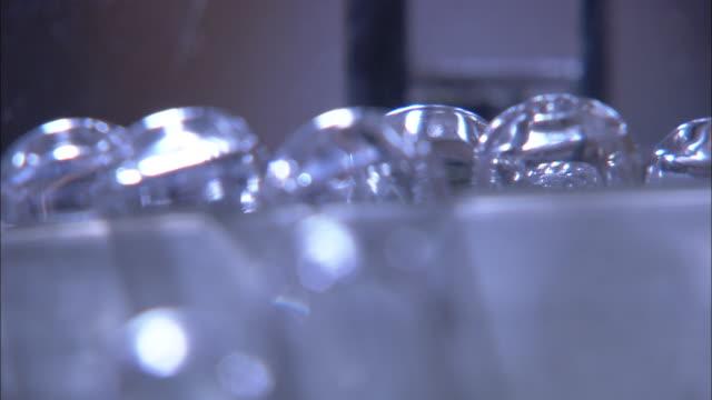 close up rack-focus static - test tubes reflect light in a laboratory. / bloemfontein, south africa - vetreria da laboratorio video stock e b–roll