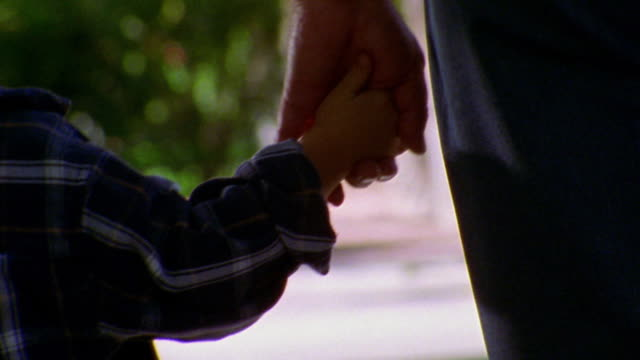 close up REAR VIEW man holding hands with young boy + walking away from camera outdoors