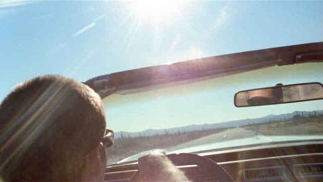vidéos et rushes de close up rear view of man driving convertible / tilt up sun shining overhead / baja, mexico - aller tranquillement