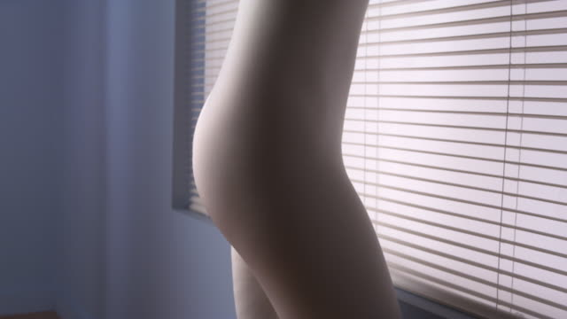Close up rear view of woman standing in living room