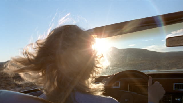 close up rear view woman driving convertible in desert / baja, mexico - オープンカー点の映像素材/bロール