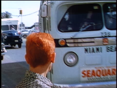 vídeos y material grabado en eventos de stock de 1957 close up rear view woman with red hair watching as bus pulls up to stop on street - 1957