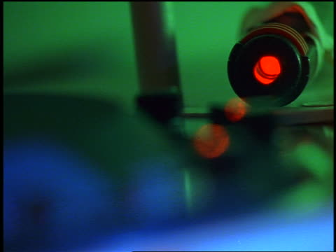 close up red laser operating on test tube machine