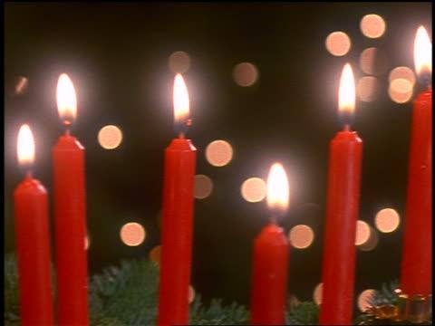 close up pan red lit candles amongst pine branches indoors - einige gegenstände mittelgroße ansammlung stock-videos und b-roll-filmmaterial