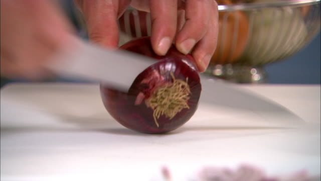 Close up red onion being lifted from basket / zoom in onion being sliced on cutting board / Auckland
