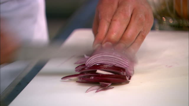 Close up red onion being sliced on cutting board and lifted into bowl / Auckland, New Zealand