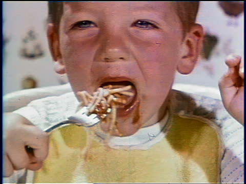 1969 close up redheaded boy eating spaghetti + getting mouth dirty / industrial - tomatensoße stock-videos und b-roll-filmmaterial