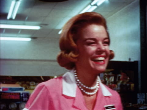 1965 close up redheaded female cashier smiling + talking in grocery store / educational
