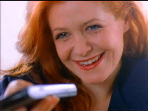 close up redheaded woman watching TV points remote control + presses buttons / sneers + laughs