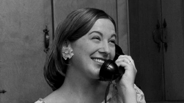 close up reenactment woman smiling while talking on telephone, then cupping receiver and calling out - 1955 stock videos & royalty-free footage