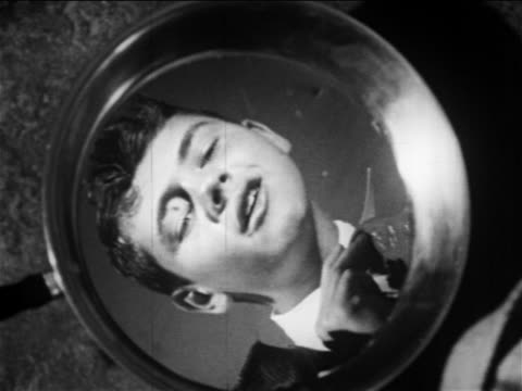 b/w 1949 close up reflection in cooking pan of boy adjusting tie / educational - one teenage boy only stock videos & royalty-free footage