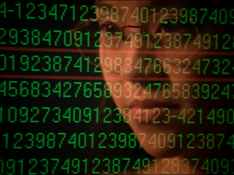 close up reflection of Asian woman with eyeglasses in computer screen with green numbers moving