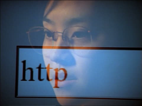 close up reflection of Asian woman with eyeglasses in computer screen typing out Internet address