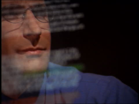 pan close up reflection of businessman wearing eyeglasses in computer screen with scrolling text - nur männer über 30 stock-videos und b-roll-filmmaterial