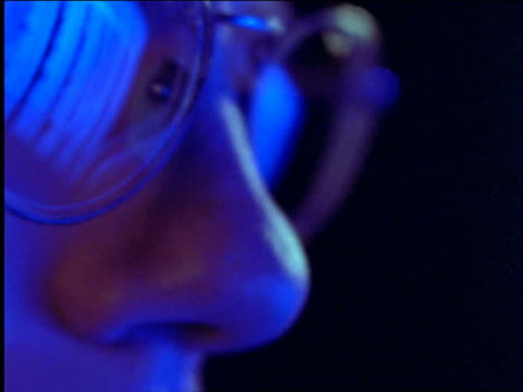 close up reflection of computer screen in man's eyeglasses / Blue light