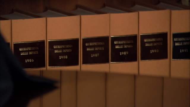 Close up reflection of law books on table/ tilt up close up lawyer turning to look at camera/ lawyer looking at camera/ Rome