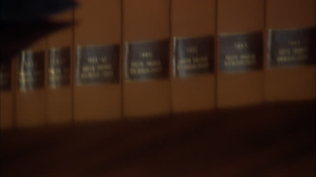close up reflection of law books on table/ tilt up close up lawyer turning to smile at camera/ rome - legge video stock e b–roll