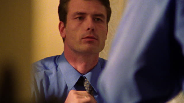 close up reflection of man adjusting tie in mirror