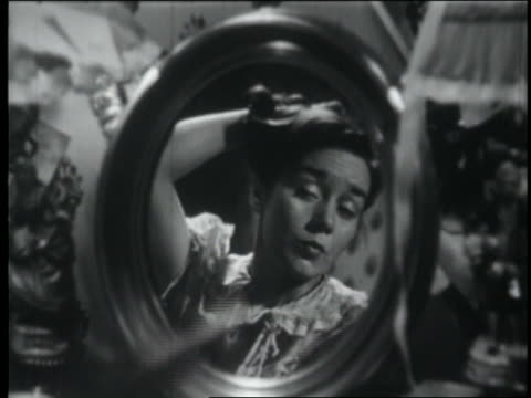 vídeos y material grabado en eventos de stock de b/w 1951 close up reflection of teen girl pretending to be glamorous in mirror / starts laughing - sólo chicas adolescentes