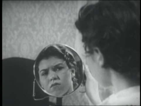 stockvideo's en b-roll-footage met b/w 1951 close up reflection of teen girl with hair in pins looking in hand mirror with disgusted expression - spiegel