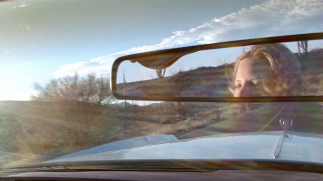 close up reflection of woman driving convertible through desert in rear view mirror / baja, mexico - auto convertibile video stock e b–roll