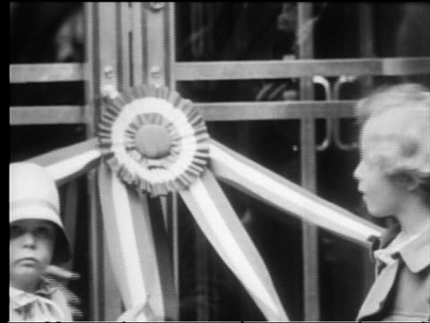 vídeos de stock e filmes b-roll de b/w 1931 close up ribbon falling off of door on empire state building at dedication / children in foreground - 1931