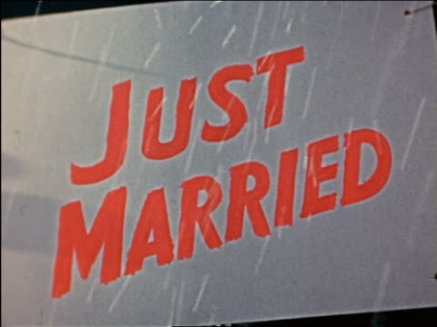 "1941 close up rice falling on ""just married"" sign on trunk of car driving away from camera / industrial - wedding ceremony stock videos & royalty-free footage"