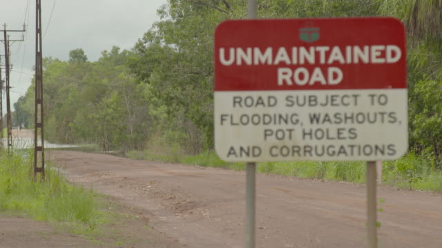 close up road sign 'Unmaintained Road Road Subject to Flooding Washouts Pot Holes and Corrugations' / wider shot sign seeing roadway behind leading...