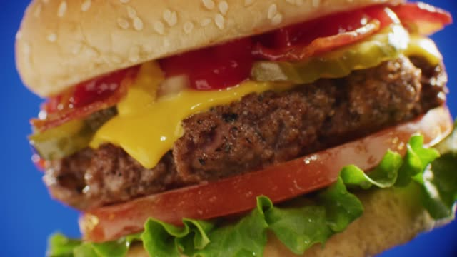 close up; rotating bacon cheeseburger with pickle tomato and lettuce shot over blue screen. - ethik und moral stock-videos und b-roll-filmmaterial