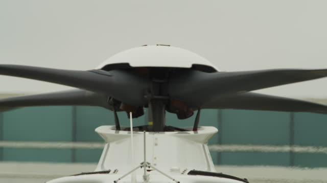 close up rotors on a helicopter start to spin, heat waves shimmer in the background as it prepares for takeoff. - helicopter rotors stock videos and b-roll footage