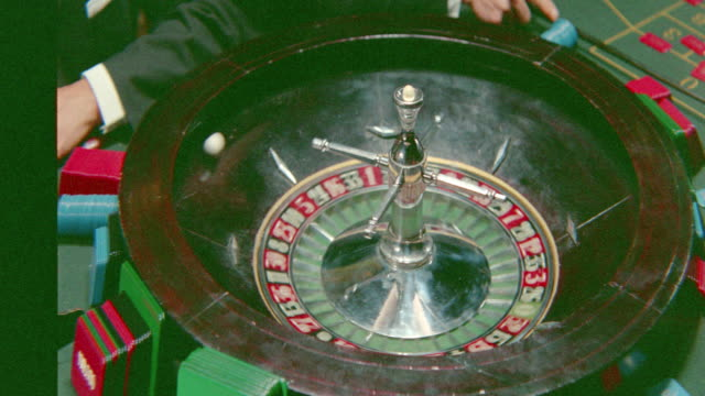 close up roulette wheel stops spinning, ball stops on number / three bites of the apple (1966) - roulette stock videos and b-roll footage