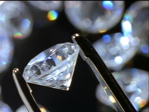 vidéos et rushes de close up round cut diamond held by tweezers with diamonds in background - diamant pierre précieuse