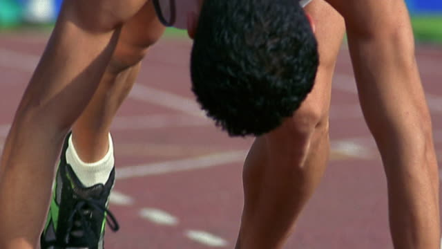 close up runner taking his place at starting blocks before race - sheppard132点の映像素材/bロール